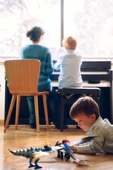 Famiglia felice di trascorrere del tempo insieme. ragazzino che gioca sul pavimento di casa con giocattoli nuovi di zecca