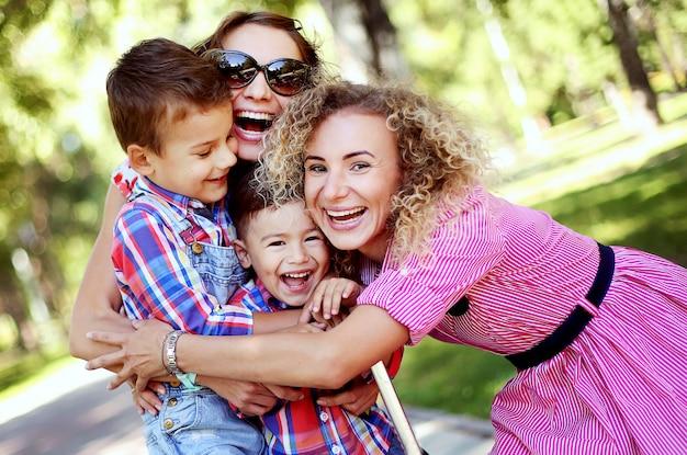 Famiglia felice nel parco estivo. donne e bambini che abbracciano e sorridono.