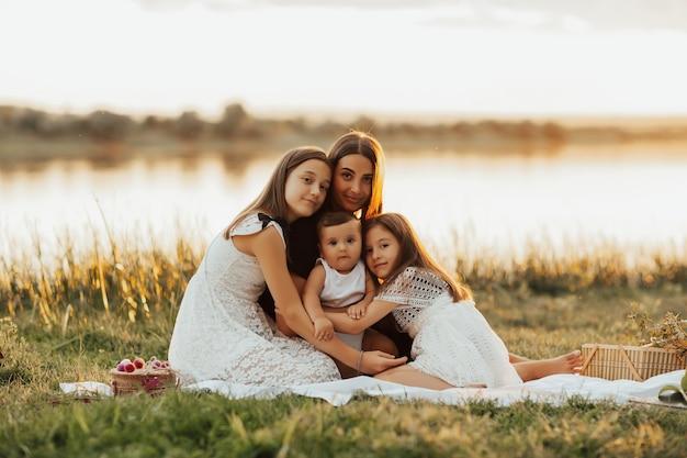 Famiglia felice sul picnic estivo vicino al fiume nella soleggiata giornata estiva