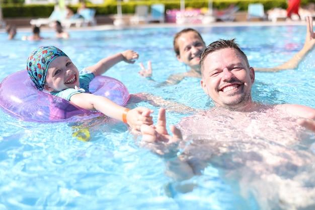 Famiglia felice nuotare in piscina con acqua blu trasparente.