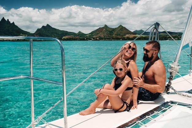 Una famiglia felice in costume da bagno siede su un catamarano nell'oceano indiano. ritratto di una famiglia su uno yacht nella barriera corallina dell'isola di mauritius.