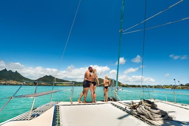 Una famiglia felice in costume da bagno si trova su un catamarano nell'oceano indiano. ritratto di una famiglia su uno yacht nella barriera corallina dell'isola di mauritius