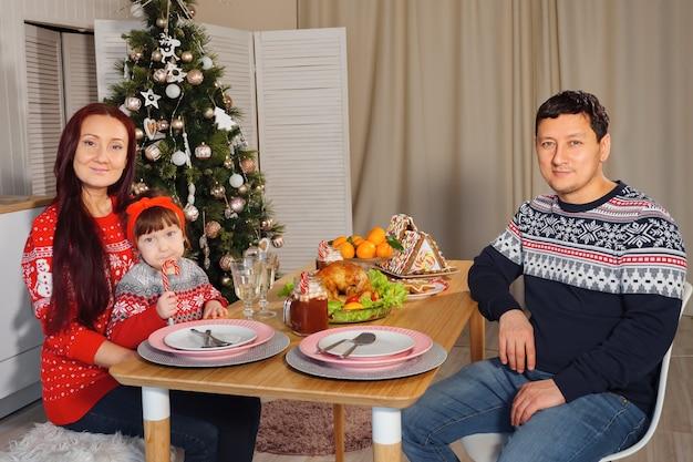 Famiglia felice a tavola sullo sfondo di un albero di natale decorato