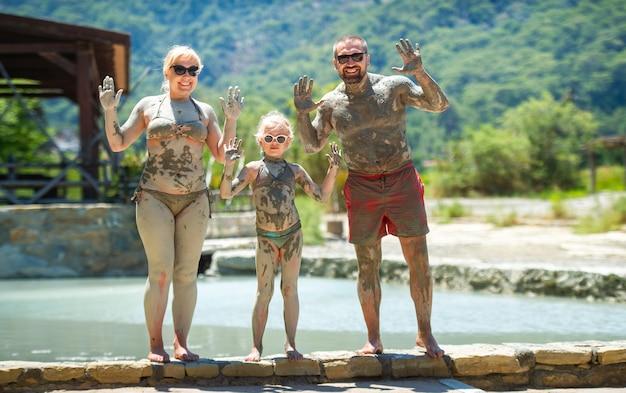 Una famiglia felice fa un bagno di fango in un resort in turchia. benessere familiare nel fango terapeutico