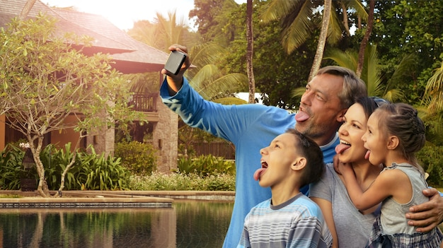 Famiglia felice che prende selfie sulla spiaggia del mare