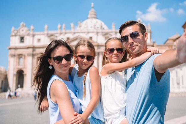 Famiglia felice che prende selfie a città del vaticano e nella chiesa della basilica di st peter, roma, italia