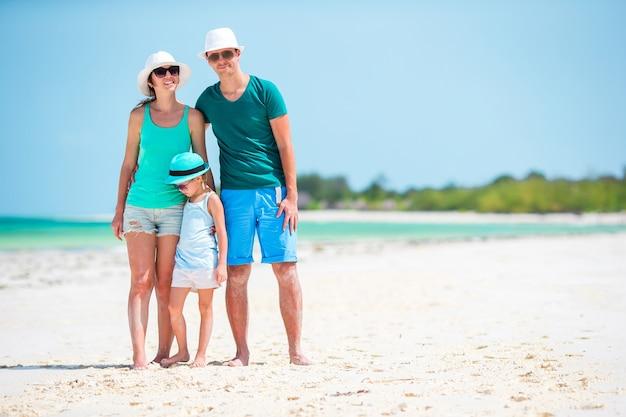 Felice famiglia di tre persone su una spiaggia durante le vacanze estive