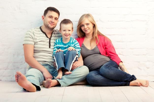 Felice famiglia di tre persone seduto sul pavimento vicino al muro