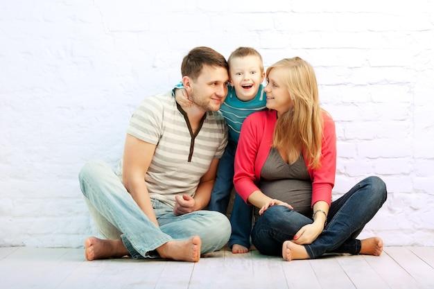 Una famiglia di tre felice che si siede sul pavimento