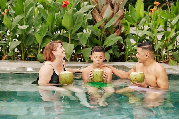 Felice famiglia di tre persone seduti in piscina e bere rinfrescanti cocktail di cocco