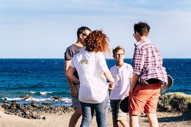 Famiglia felice insieme e abbracciata in spiaggia davanti e guardando il mare - quattro persone - bambino e adolescente - millenario con skateboard in braccio
