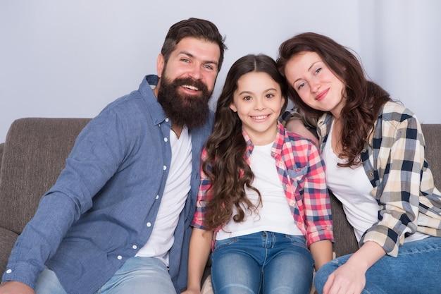 Famiglia felice insieme. bambina con i genitori. fiducia e relativi vincoli. uomo barbuto e donna con bambino. la famiglia felice si rilassa a casa. weekend in famiglia. madre e padre amano figlia figlia.