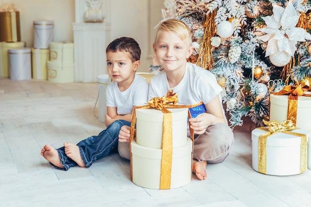 Il ragazzo felice dei due bambini della famiglia si rilassa giocando vicino all'albero di natale alla vigilia di natale a casa. fratelli in una stanza luminosa con decorazioni invernali. natale capodanno tempo per la celebrazione.