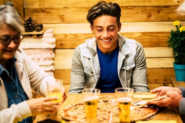Famiglia felice di due anziani e un adolescente a casa o al ristorante che mangiano pizza e bevono birra insieme - tavolo di legno