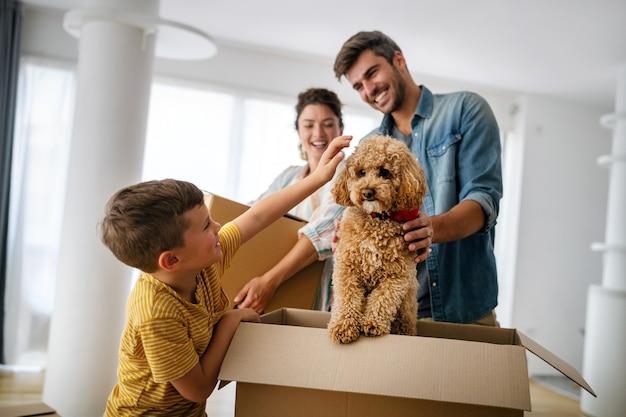 Famiglia felice che disimballa le scatole nella nuova casa il giorno del trasloco. persone, immobili, nuovo concetto di casa
