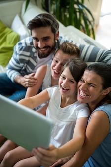 Famiglia felice che utilizza compressa digitale nel salone