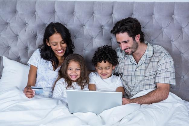 Famiglia felice che per mezzo del computer portatile sul letto