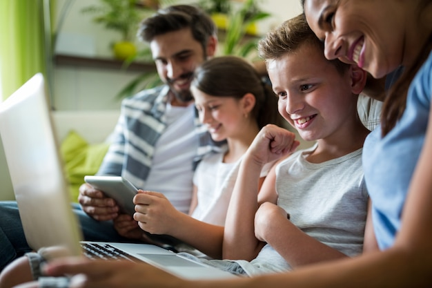 Famiglia felice che utilizza computer portatile e compressa digitale nel salone