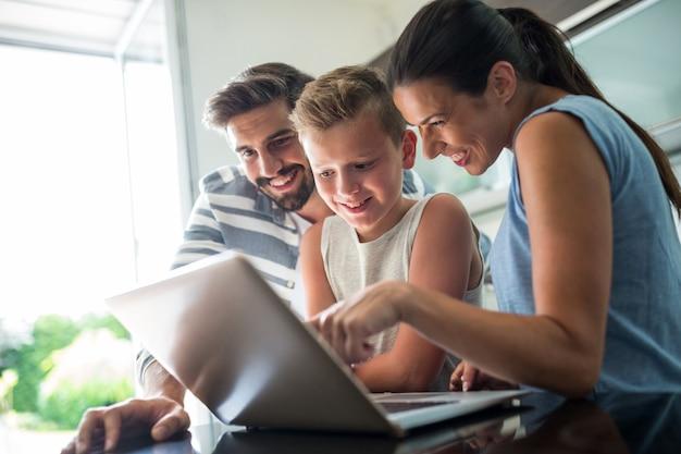 Famiglia felice che utilizza computer portatile nel salone