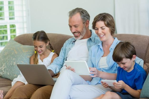 Famiglia felice utilizzando il telefono cellulare, tablet digitale e laptop in soggiorno