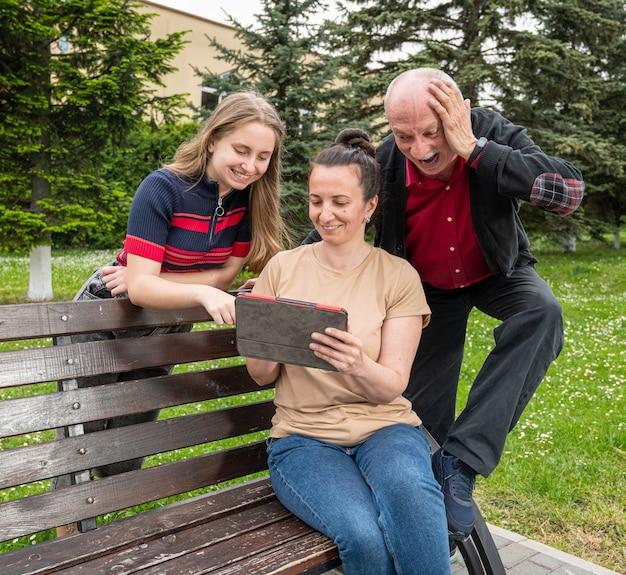Famiglia felice che utilizza tablet pc all'aperto nel parco