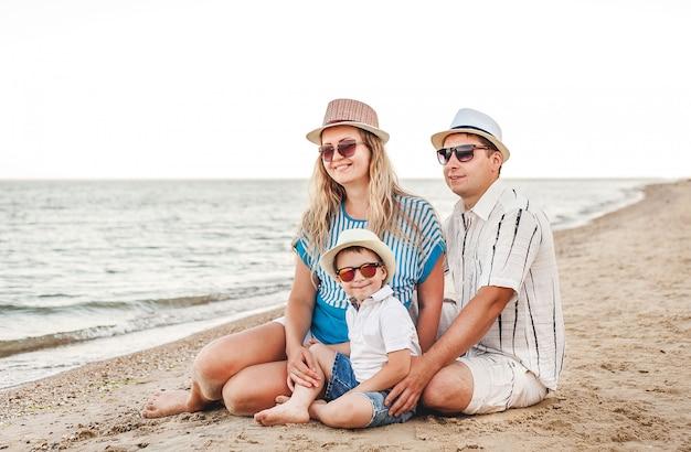 Famiglia felice in vacanza. sulla spiaggia si trovano mamma, papà e un figlio piccolo. famiglia in viaggio. baci, sorrisi