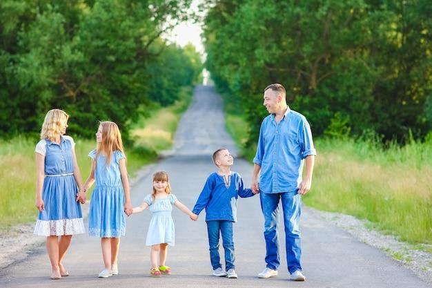 Una famiglia felice cammina lungo la strada nel parco sullo sfondo della natura