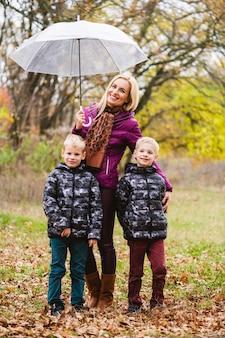 Famiglia felice a piedi al parco autunnale durante la pioggia. madre con gemelli maschi a sfondo colorato natura caduta. la mamma protegge dalla pioggia con l'ombrello trasparente, i ragazzi con le giacche simili