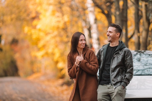 Famiglia felice che cammina nel parco di autunno il giorno soleggiato dell'autunno