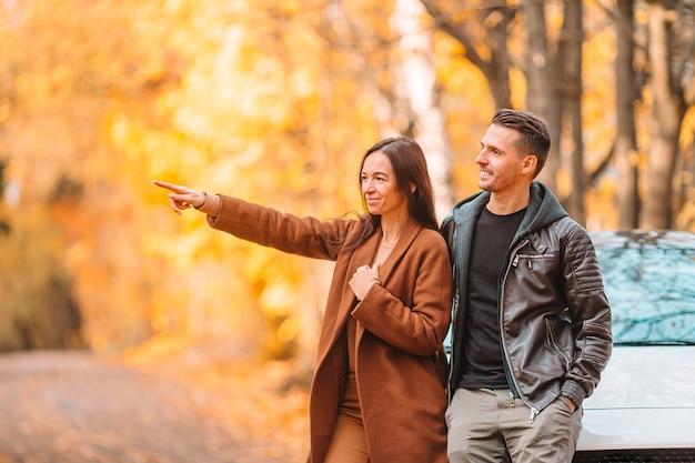 Famiglia felice che cammina nella sosta di autunno sulla giornata di sole autunnale
