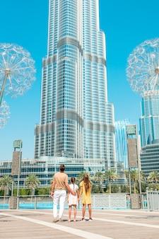 Famiglia felice che cammina nel dubai con il grattacielo burj khalifa