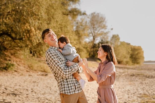 Famiglia felice che cammina sulla strada nel parco. padre, madre che tiene il figlio del bambino sulle mani e andare insieme. retrovisore. concetto di legami familiari.
