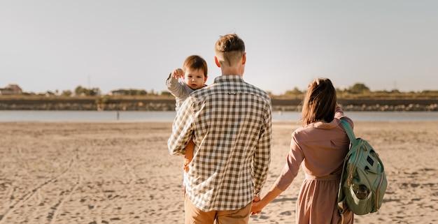 Famiglia felice che cammina sulla spiaggia sabbiosa del fiume. padre, madre che tiene il figlio del bambino sulle mani e andare insieme. retrovisore. concetto di legami familiari.