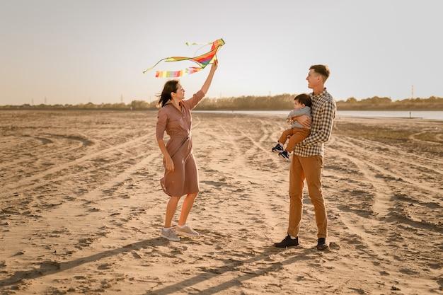 Famiglia felice che cammina sulla spiaggia sabbiosa del fiume. padre, madre che tiene in braccio il figlio del bambino e gioca con l'aquilone.