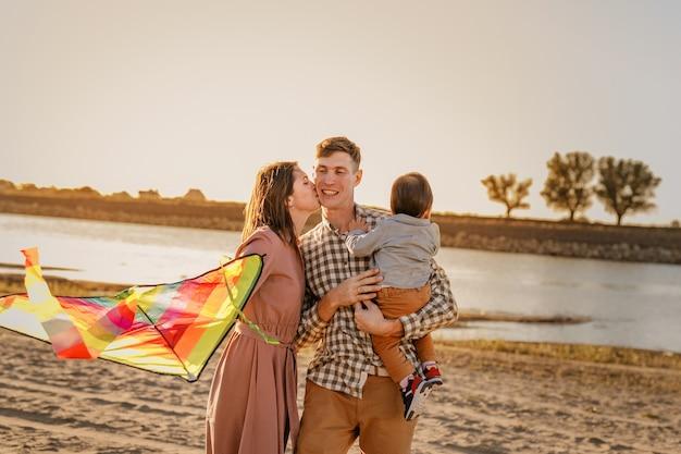 Famiglia felice che cammina sulla spiaggia sabbiosa del fiume