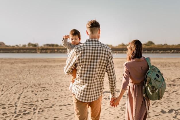 Famiglia felice che cammina sulla spiaggia sabbiosa