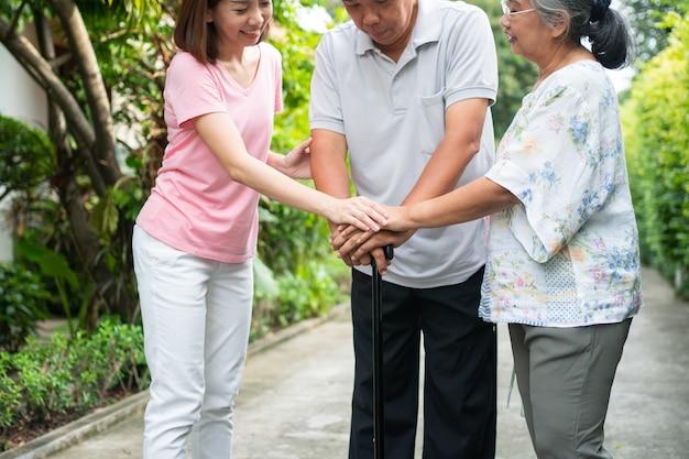 Famiglia felice che cammina insieme nel giardino. anziani anziani che usano un bastone da passeggio per aiutare a camminare in equilibrio. concetto di amore e cura della famiglia e assicurazione sanitaria per la famiglia