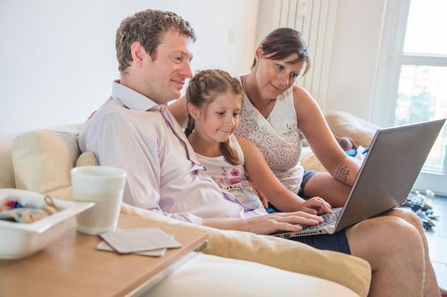 La famiglia felice guarda il pc che si siede sul divano