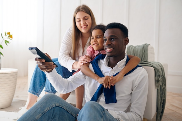 Famiglia felice che guarda la tv in soggiorno