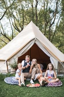 Famiglia felice che indossa abiti boho cowboy, padre, madre e due figlie seduti su cuscini sull'erba e mangiare anguria.