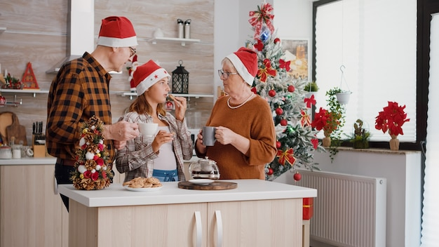 Famiglia felice che indossa il cappello di babbo natale che celebra le vacanze del giorno di natale mangiando biscotti al cioccolato al forno