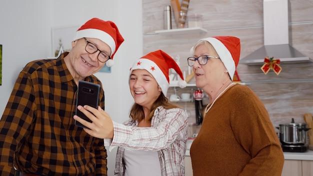 Famiglia felice che indossa il cappello di babbo natale che si gode la stagione invernale discutendo insieme con gli amici remoti