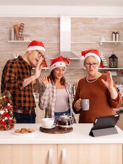 La famiglia felice che indossa il cappello di babbo natale saluta i genitori remoti che si godono le vacanze di natale