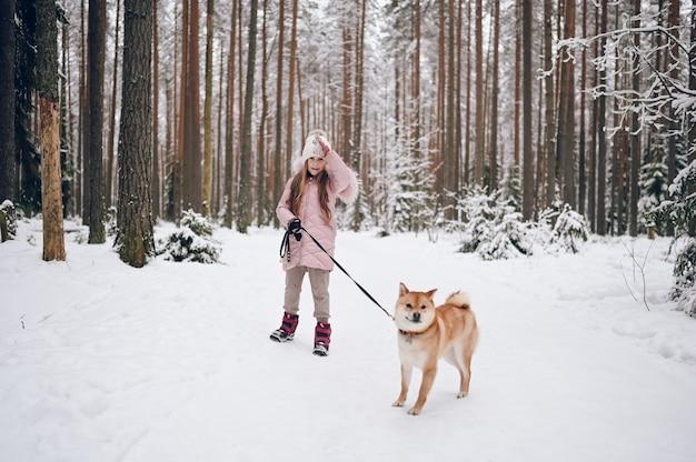 Fine settimana felice della famiglia - piccola ragazza sveglia in outwear caldo rosa che cammina divertendosi con il cane rosso di shiba inu nella foresta di inverno freddo bianco nevoso all'aperto