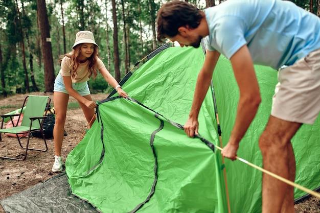 Famiglia felice in un fine settimana in una pineta. una coppia di innamorati monta una tenda e si accampa. campeggio, ricreazione, escursionismo.