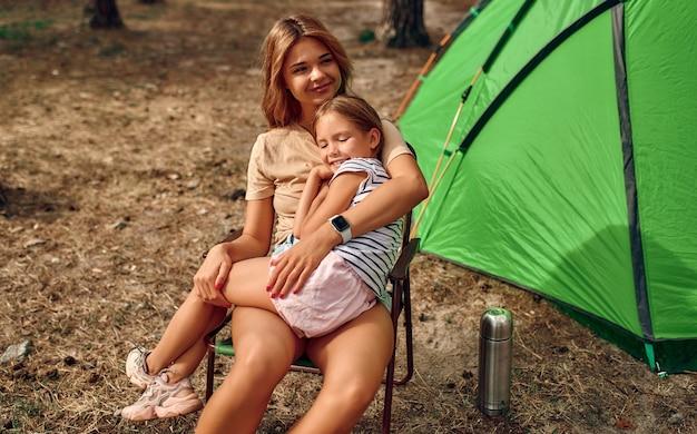 La famiglia felice in un fine settimana in una pineta ha montato una tenda. bambina che aiuta i genitori ad allestire l'accampamento. campeggio, ricreazione, escursionismo.