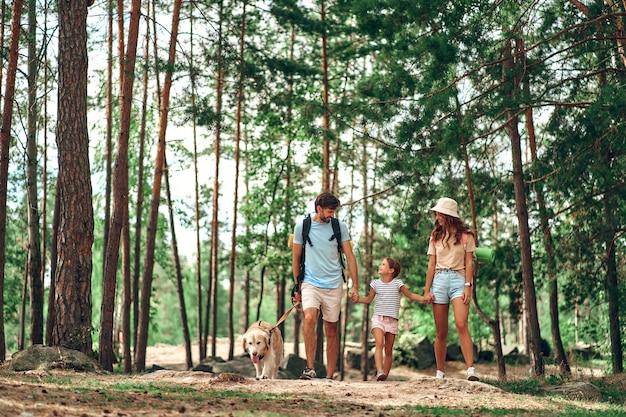 La famiglia felice con gli zaini e il cane labrador cammina nella foresta. campeggio, viaggi, escursioni.