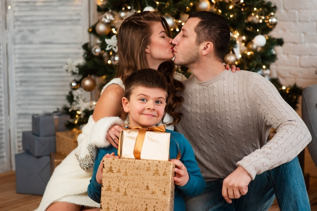 Una famiglia felice con un bambino festeggia il natale. i genitori e un bambino si siedono sul pavimento vicino all'albero di natale in un ambiente domestico e si scambiano regali. il bambino sorride e gioisce in famiglia