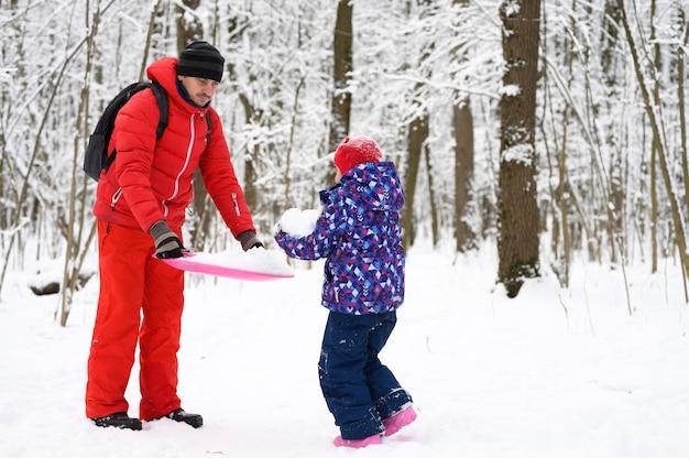 La famiglia felice con i bambini si diverte a trascorrere le vacanze invernali nella foresta invernale innevata. padre gioca con sua figlia