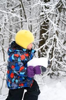 La famiglia felice con i bambini si diverte a trascorrere le vacanze invernali nella foresta invernale innevata. ragazzino ragazzo gioca allegro